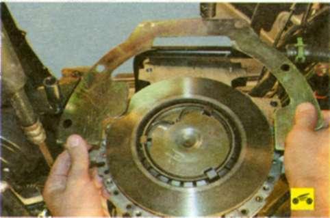 Снимите щиток картера сцепления с направляющих втулок в блоке цилиндров